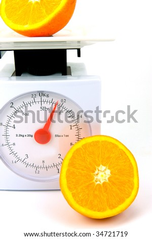 A sliced orange on top of a set of kitchen scales isolated against a white background