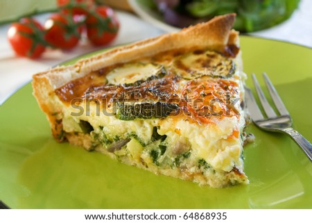 A sliced portion of Zucchini quiche on a plate - stock photo