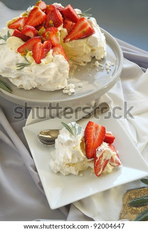 A sliced serving of strawberry pavlova ready to go to the table. - stock photo