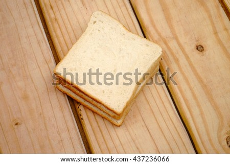 A slices of whole bread on wooden background. - stock photo