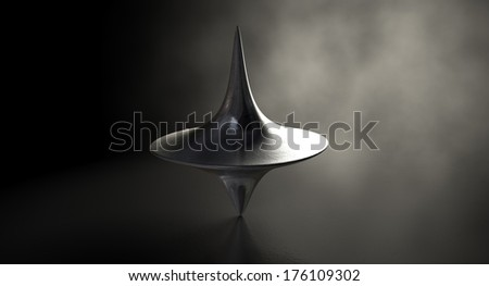 A slightly scratched die-cast lead spinning top in an upright position on a dark background with an eerie back light - stock photo
