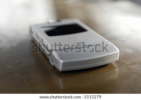 A slim cellular phone handset lying on a countertop