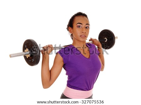 A slim pretty african american woman lifting weight, standing isolatedfor white background with the weight behind her head. - stock photo