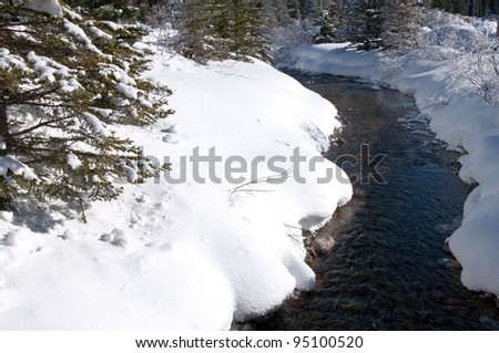 A slow moving shallow creek with untouched snow and ice along its banks - stock photo