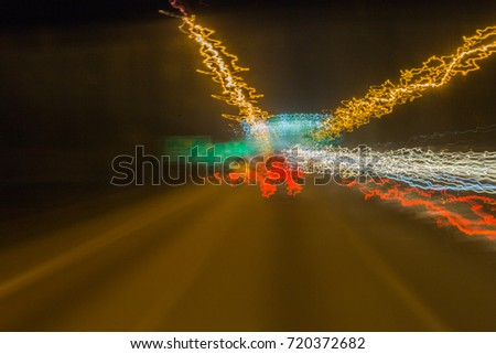 A slow shutter images of vehicles on a highway taken from a moving bus.