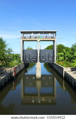 A sluice is a water channel controlled at its head by a gate. A sluice gate is traditionally a wood or metal barrier sliding in grooves that are set in the sides of the waterway. - stock photo