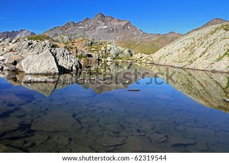 A small alpin lake at 2800 meters on the sea-level near Gavia Pass, Brixia province, Lombardy region, Italy. - stock photo