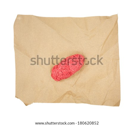A small amount of ground sirloin hamburger on brown butcher paper. - stock photo