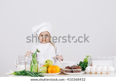 A small and funny little girl in a cap cook with fresh food in the kitchen on a white background