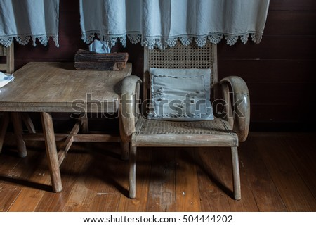 A small antique wooden chair sits on hardwood floor.