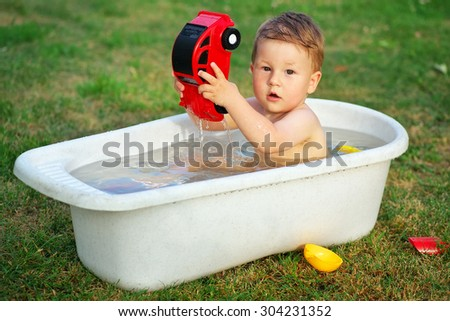 A small baby bathed in the bath and playing with toy car. - stock photo