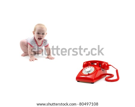 A small baby girl and a red telephone