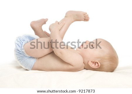 A small baby girl lying on a blanket grabbing her foot smiling at the camera bashfully.