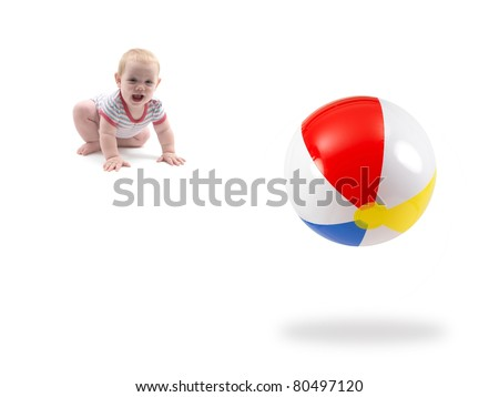 A small baby girl playing with a beach ball