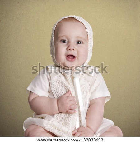 a small baby, with her ??dress to celebrate her christening