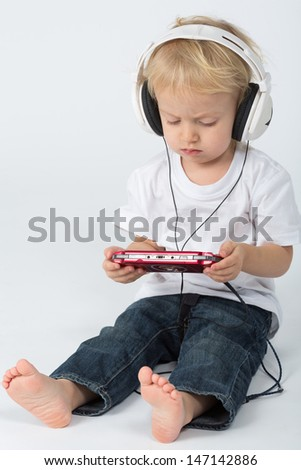 A small barefoot boy in blue jeans with headphones playing the game device