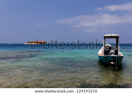 A small boat anchored in the foreground, with a tiny caribbean island visible in the background in the Islas del Rosario, near Cartagena de Indias, Colombia - stock photo