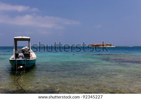 A small boat anchored in the foreground, with a tiny caribbean island visible in the background in the Islas del Rosario, near Cartagena de Indias, Colombia