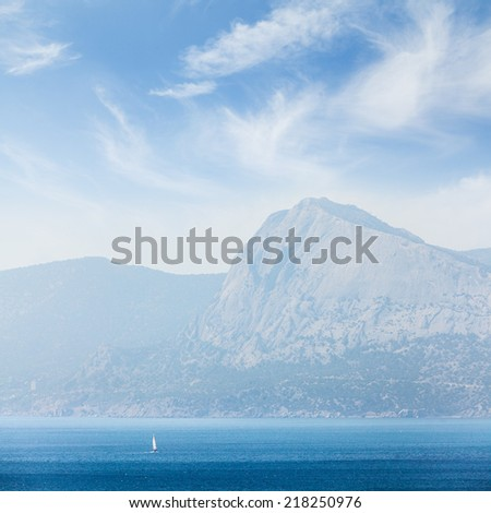 A small boat or yacht sailing on the sea at day on a background mountains and sky with clouds. - stock photo