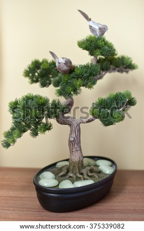 A small bonsai tree in black ceramic pot on wooden table, on yellow background. Bonsai tree with small swallows on branches and pearly white rocks around his stem - stock photo