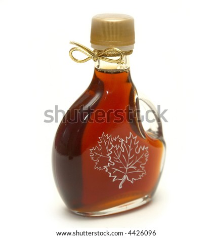 A small bottle of maple syrup with the maple leaves printed on the front and a nice golden ribbon on the neck! - stock photo