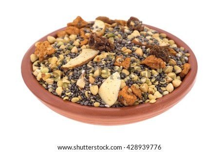 A small bowl filled with dry breakfast cereal consisting of chia seeds, nuts, and dried fruit isolated on a white background. - stock photo