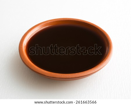 A small bowl filled with mesquite flavored liquid seasoning for cooking on a white cutting board. - stock photo
