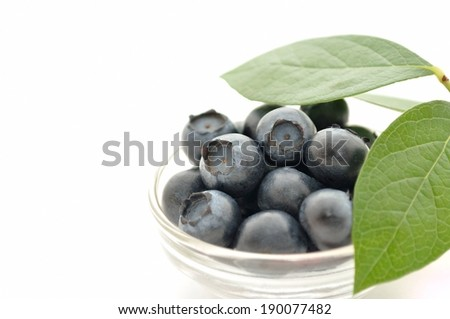 A small bowl of fresh ripe blueberries with garnish. - stock photo