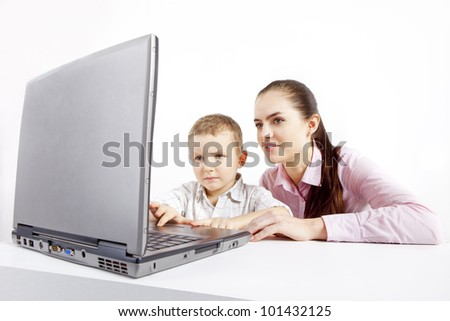 A small boy and beautiful  woman sitting at the front of laptop. Boy learns use it. He is very concentrated. She is helping him in learning.