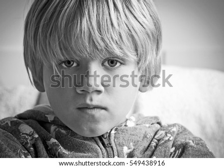 A small boy depicting the emotion of worry by having a concerned expression