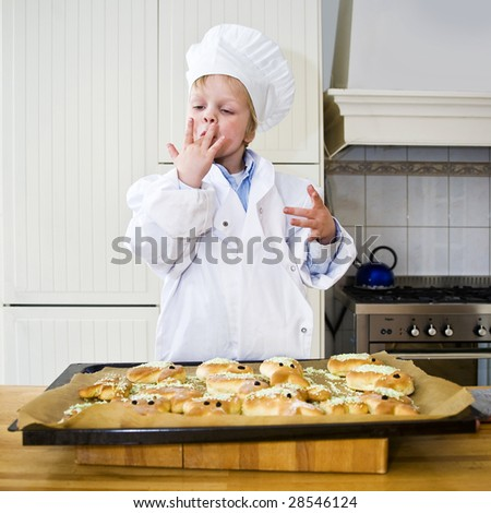 A small boy, dressed as a chef, licking his fingers, illustrating how good the bread he baked will taste