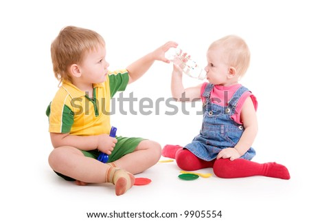 a small boy gives water in a bottle to the small girl