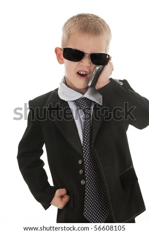A small boy in the studio, dressed up in a suit and pretending to be a businessman. - stock photo