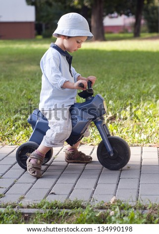 A small boy learning to ride his first plastic toy bike.