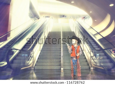 a small boy next to stairs and an escalator at an airport