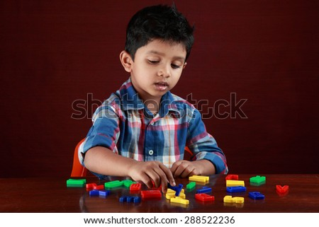A small boy plays with toy alphabets in dark background - stock photo