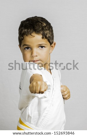 A small boy punching wile dressed in karate uniform. - stock photo