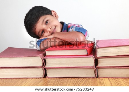 A small boy resting his head on big books - stock photo