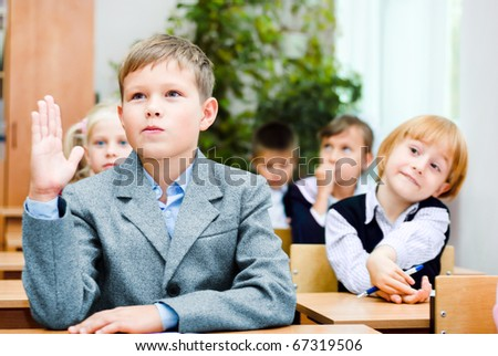 A small boy sits at the desk - stock photo