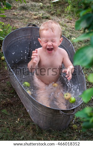 A small boy sits in a bath outdoors