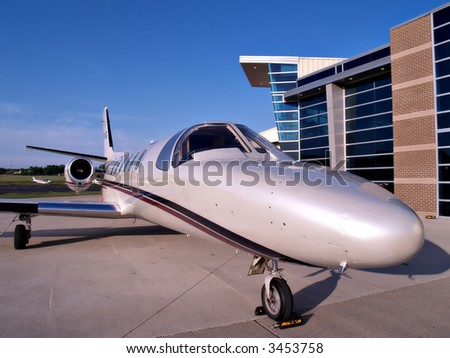 A small business jet waits on the tarmac for its passengers - stock photo