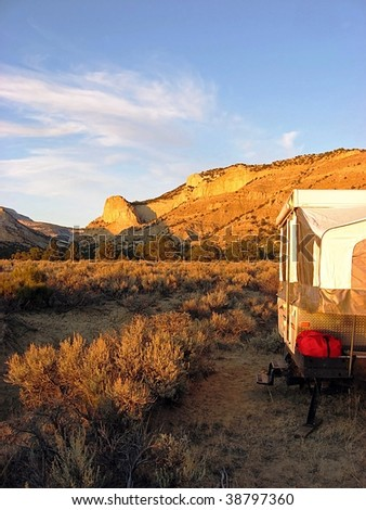 A small camp trailer parked in a desert area near a cliff wall. - stock photo
