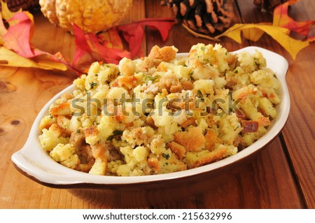 A small casserole dish of cornbread stuffing on a rustic wooden table with autumn leaves and pine cones - stock photo