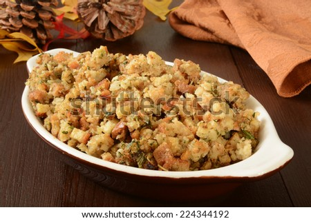 A small casserole dish of herbal holiday stuffing in turkey juice - stock photo