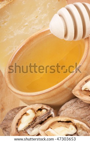 A small ceramic cup full of honey ready to be served with pecorino cheese and walnuts. Studio shot.