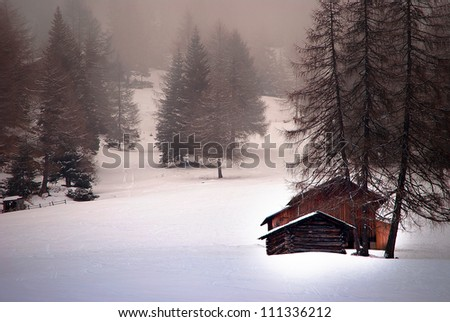 A small chalet in a foggy day on the mountains - stock photo