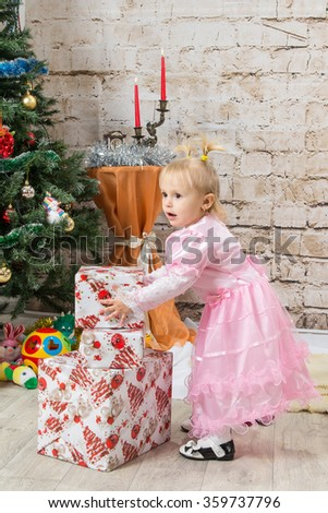 A small child - a girl unpacks near a Christmas tree Christmas gifts