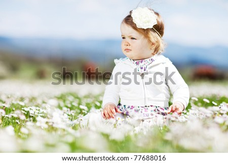A small child in a field of flowers - stock photo