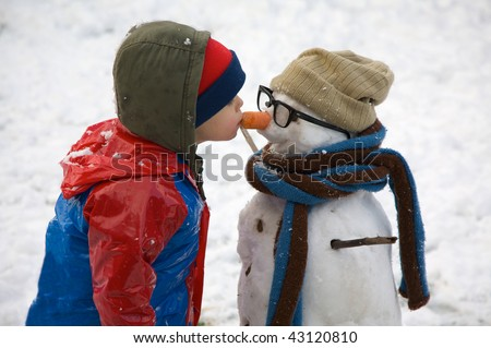 A small child kisses his snowman on the nose, which is a carrot!