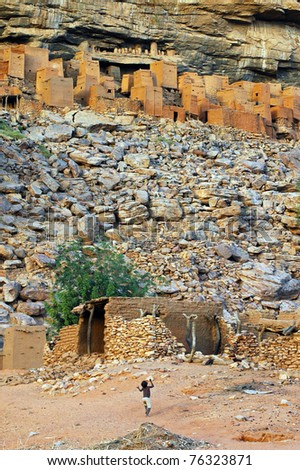 A small child playing in front of ancient Dogon and Tellem houses at the base of the Bandiagara escarpment in Mali